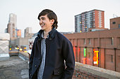 Smiling man looking away on urban rooftop - Stock Image - E5M0D8