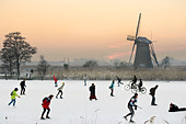 Ice skaters and even cyclists on natural ice in front of a windmill at Kinderdijk Holland, The Netherlands. At sunset. - Stock Image - B7YXC6