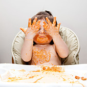 Happy baby having fun eating messy showing hands covered in Spaghetti Angel Hair Pasta red marinara tomato sauce. - Stock Image - C2606D