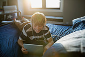 Boy with headphones using digital tablet on bed - Stock Image - FJX5FW