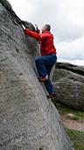rock climber Doug Blane bouldering at Burbage Edge South, Derbyshire, Peak District National Park, England, UK, United, Kingdom, - Stock Image - DC873D