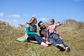 A young family having fun on the sand dunes at Horsey Beach on the Norfolk coast. - Stock Image - DYDCR4