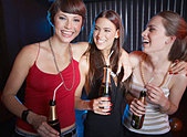 Three women in a nightclub drinking and laughing - Stock Image - B0K8F0