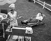 1950s 1960s WOMAN IN CHEF'S HAT AND APRON GRILLING HOT DOGS ON GRILL MAN IN CHAISE LONGUE LAUGHING EATING A FRANKFURTER OUTSIDE - Stock Image - CMR4GP