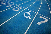 Handicap wheelchair icon superimposed on top of running track. - Stock Image - C4N872