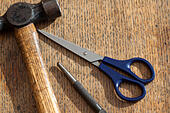 Ball pein hammer, scissors and a centre/centrer punch on a wooden surface - Stock Image - HG7MTE
