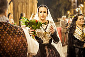 Valencia, Spain. March 18th, 2014: A Fallera finally offers her flower bouquet to the Virgin and hands it over to be placed at the virgins image. © matthi/Alamy Live News - Stock Image - DX6589