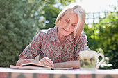 Woman writing in journal at patio table - Stock Image - BTB5X0
