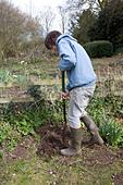 Model released teenage boy digging hole in garden - Stock Image - BK7G1E