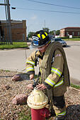 Female firefighter in rural volunteer fire department working with equipment. - Stock Image - EXHXB0