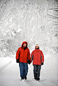 A couple in matching red winter coats walking in a Cotswold lane in snowy conditions UK - Stock Image - CEJEXH