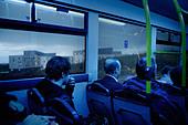 Passengers on a bus lit by blue light near Edinburgh Scotland - Stock Image - B732H2