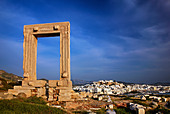 The Portara (temple of Apollo) and the Chora ('capital') of Naxos island in the background. Cyclades, Greece - Stock Image - CPK2RB