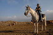 An Israeli cattle herder wearing a pistol mounted on a horse in the Golan heights northern Israel - Stock Image - AN7MRK
