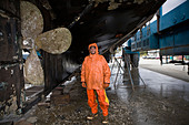 Palmer Robert pressure washes the bottom of an 88 feet long fishing boat Leann in the shipyard in Port Townsend - Stock Image - B3JPEH