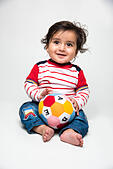 Indian baby boy playing over over white background and looking at camera - Stock Image - HTAW34