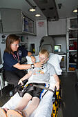 Female paramedic assisting young male patient in back of ambulance. - Stock Image - EXGTHR