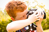A Young boy, aged 7, using a digital SLR camera in a sunny garden. - Stock Image - CBH1HT