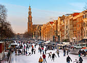 Amsterdam Ice Skating on a frozen Canal in winter. Prinsengracht Canal with Westertoren Tower and Westerkerk - Stock Image - EDNF88