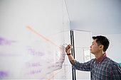 Businessman writing on whiteboard - Stock Image - EJRW8K