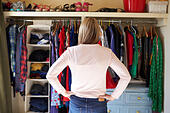 Woman In Bedroom Looking At Clothes In Wardrobe - Stock Image - G2TNK8
