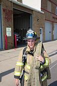 Female firefighter in rural volunteer fire department working with equipment. - Stock Image - EXHTT0