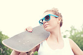 Young woman in blue sunglasses with a skateboard in the daytime. Outdoors - Stock Image - D8J348