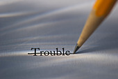 Studio shot of pencil crossing out the word trouble from piece of paper - Stock Image - C3HK78