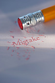 Studio shot of pencil erasing the word mistake from piece of paper - Stock Image - C3HK7G