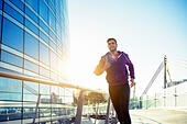 athlete with earphones running in the city - Stock Image - H7MHA2