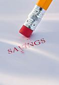 Studio shot of pencil erasing the word savings from piece of paper - Stock Image - C3HK5P