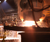 Workers Pouring Molten Steel In Plant - Stock Image - BK94PA