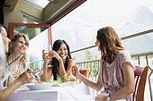 Women eating together in restaurant - Stock Image - E6RGDD