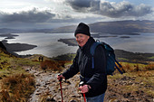 Active elderly people go hill walking in the Trossachs National Park, Scotland - Stock Image - BKW8YW