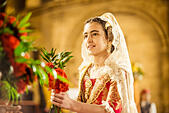 Valencia, Spain. March 18th, 2014: A young Fallera finally offers her flower bouquet to the Virgin and hands it over to be placed at the virgins image. © matthi/Alamy Live News - Stock Image - DX68R7