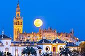 Seville Spain Seville Skyline with full moon rising behind La Giralda tower, Seville Cathedral de Sevilla, and Plaza de Toros - Stock Image - EMFD4M