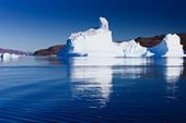 Cruising between the icebergs at Røde Ø, Scoresbysund, Greenland - Stock Image - CBY346