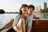 Germany, Berlin, Young couple on motor boat, laughing, portrait - Stock Image - C5WFEE