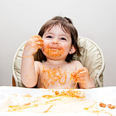 Happy smiling baby having fun eating messy covered in Spaghetti Angel Hair Pasta red marinara tomato sauce. - Stock Image - C2605B