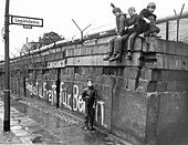 A group of children sits on the Berlin Wall at the 'Legiendamm' in the West Berlin borough Kreuzberg, March 1972. A white graffiti translates 'Unity and Freedom for Berlin'. - Stock Image - D9WJHB