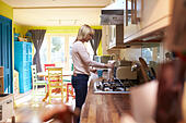 Woman Filling Kettle In Kitchen Of Stylish Apartment - Stock Image - G2TNHA