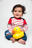 Indian baby boy playing over over white background and looking at camera - Stock Image - HTAWF9