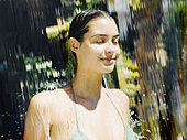 Woman in a bathing suit walking through a waterfall - Stock Image - ACCDRR