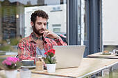 Young tattooed hipster using laptop outside cafe - Stock Image - H821GW