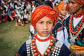 Shillong, Meghalaya - circa April 2012: Young boy wears red turban with feather and traditional costume with ornaments at Shad Suk Mynsiem Festival in - Stock Image - HGFFPE