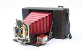 Vintage photographic film camera antique on white cut out. Folding pocket Ansco camera. red bellows - Stock Image